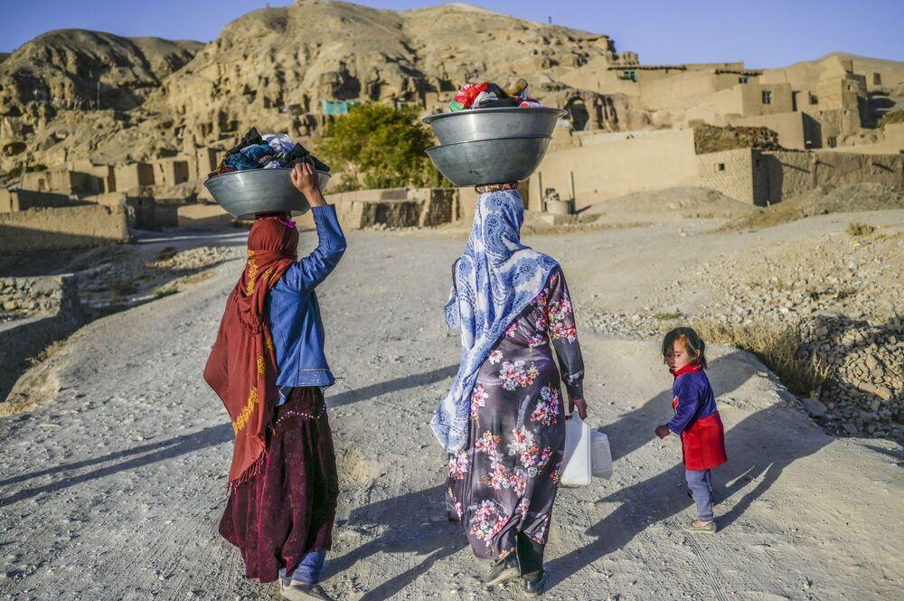 نساء، من عرقية هزارة، يحملن الملابس المغسولة يتوجهن إلى منازلهن في قرية بالقرب من جرف صخري في باميان، أفغانستان 3 أكتوبر2021