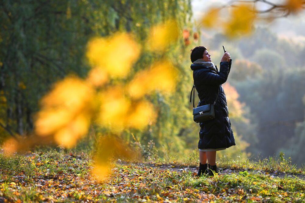 امرأة تلتقط الصور لأشجار الخريف في إحدى حدائق موسكو، روسيا 4 أكتوبر 2021