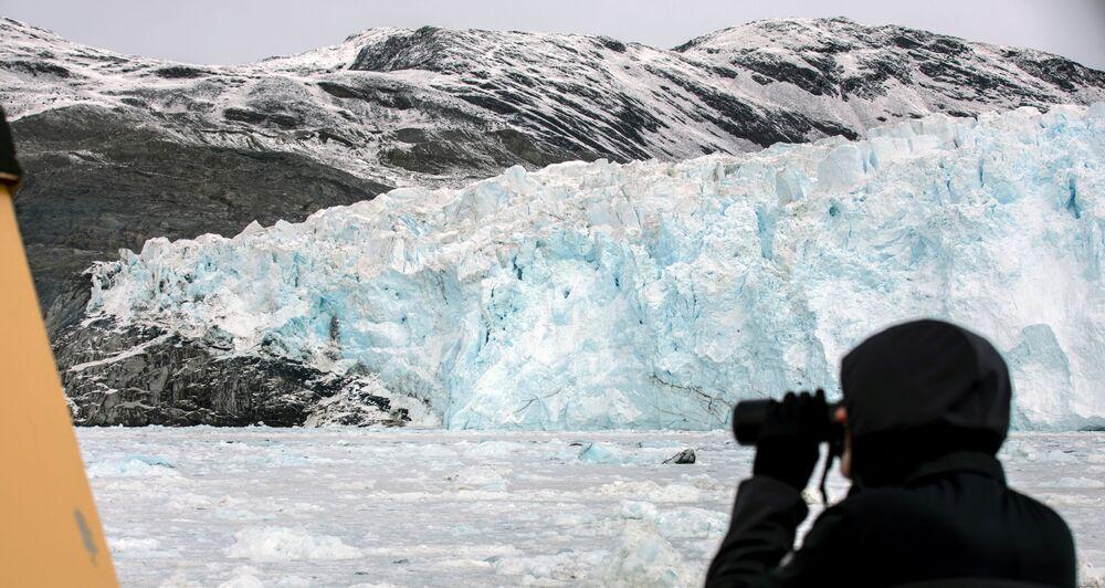 سائح يلتقط صوراً للجبل الجليدي إيكي في شمال إيلوليسات، غرينلاند ، 15 سبتمبر 2021
