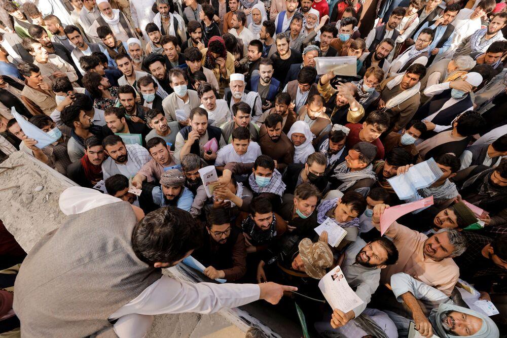 يتجمع الأفغان خارج مكتب الجوازات بعد أن أعلن مسؤولو طالبان أنهم سيبدأون في إصدار جوازات سفر لمواطنيهم مرة أخرى، بعد شهور من التأخير الذي أعاق محاولات أولئك الذين يحاولون الفرار من البلاد بعد سيطرة طالبان، في كابول، أفغانستان، 6 أكتوبر 2021.