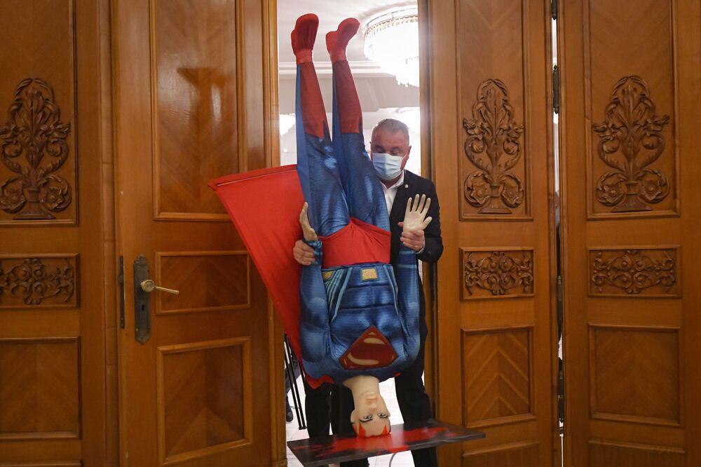 رجل يحمل تمثالًا على شكل شخصية سوبرمان قبل تصويت بحجب الثقة عن حكومة رئيس الوزراء الروماني فلورين سيتو في البرلمان الروماني في بوخارست، رومانيا 5 أكتوبر 2021.