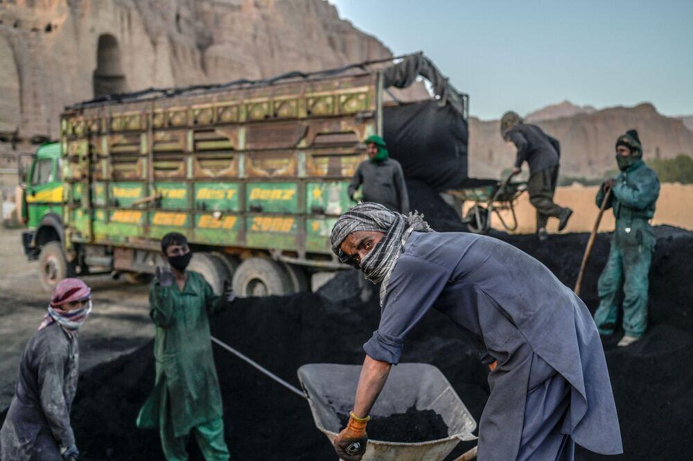 يستعد عمال الهزارة لتحميل الفحم على شاحنة بالقرب من الموقع الذي كان يقف فيه تمثال بوذا، قبل أن تدمره طالبان في مارس 2001، في مقاطعة باميان في 3 أكتوبر 2021.