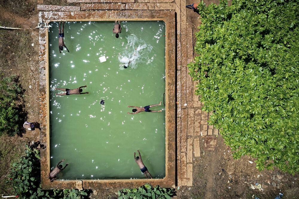 في هذه الصورة الجوية التي التقطت في 4 أكتوبر 2021، يغطس الصبيان في خزان مياه مفتوح في أرض زراعية في ضواحي بنغالور، الهند