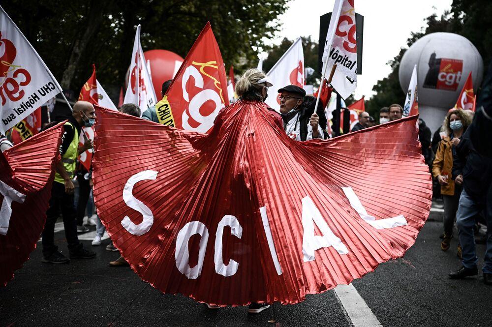 امرأة تحمل لافتة كتب عليها اجتماعي حيث يشارك الناس في مظاهرة دعت إليها النقابات الفرنسية كجزء من يوم على مستوى الدولة لتحسين ظروف العمل وضد إصلاحات المعاشات التقاعدية وصناديق البطالة، في بوردو، جنوب فرنسا في 5 أكتوبر 2021
