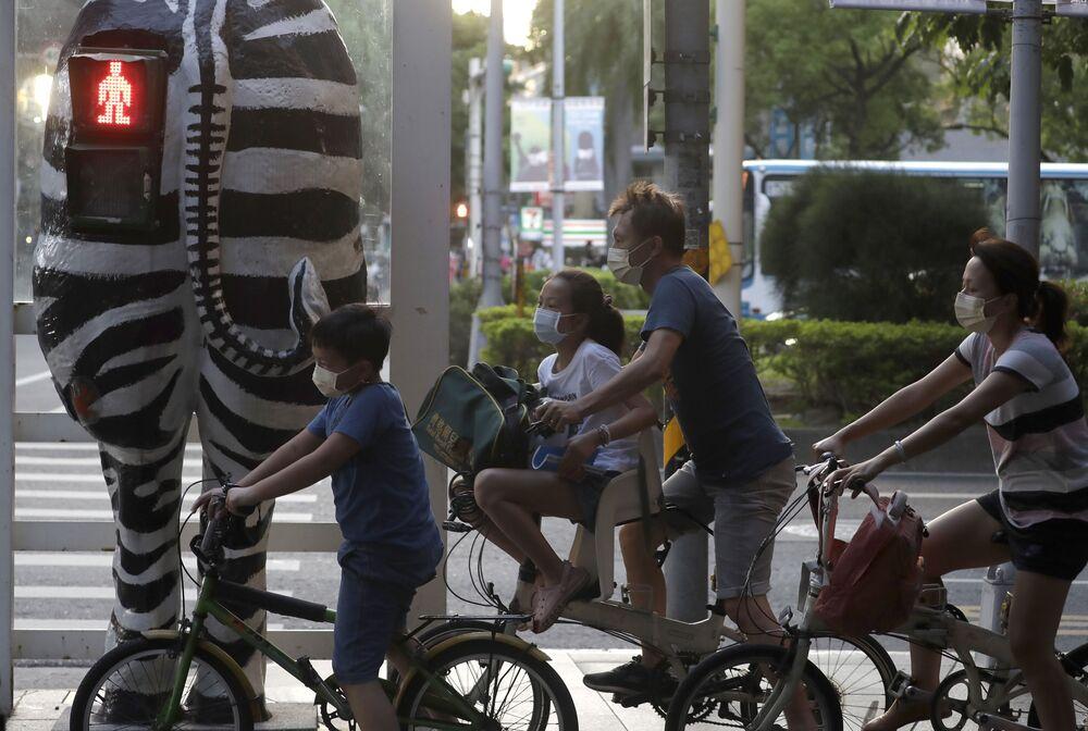 راكبو الدراجات يرتدون كمامات، ينتظرون عند إشارة مرور على شكل حمار وحشي في تايبيه، تايوان 6 أكتوبر 2021