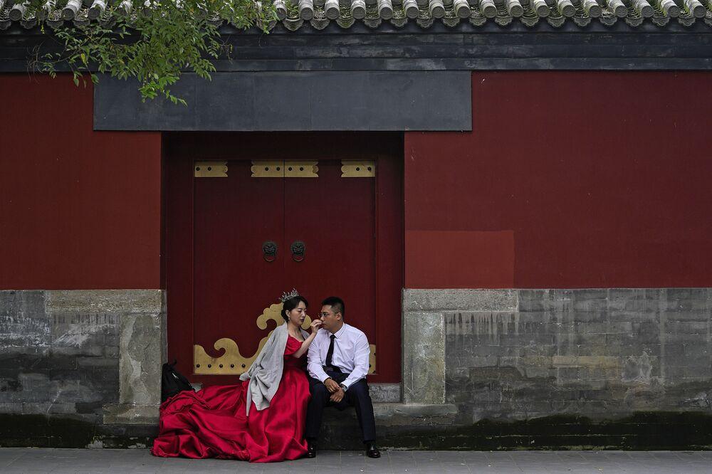 عروس تمسح وجه عريسها بينما ينتظران دورهما لالتقطا صورة لهما ما قبل الزفاف، بالقرب من المدينة المحرمة خلال عطلة العيد الوطني التي تستمر لمدة أسبوع في بكين، الصين 3 أكتوبر 2021.