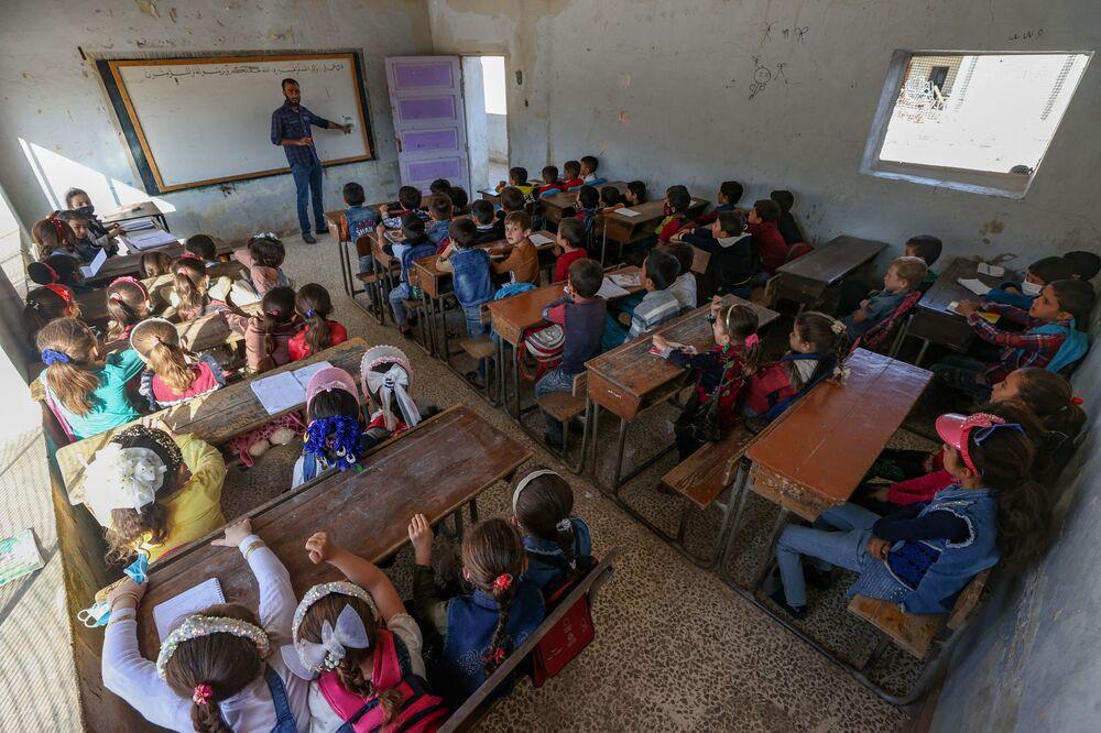 أطفال أثناء حضورهم اليوم الأول من المدرسة في قرية في ريف إدلب شمال غرب سوريا، 9 أكتوبر 2021.