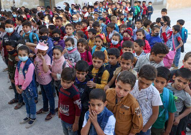 أطفال يحضرون اليوم الأول من المدرسة في قرية بريف إدلب شمال غرب سوريا، 9 أكتوبر 2021.