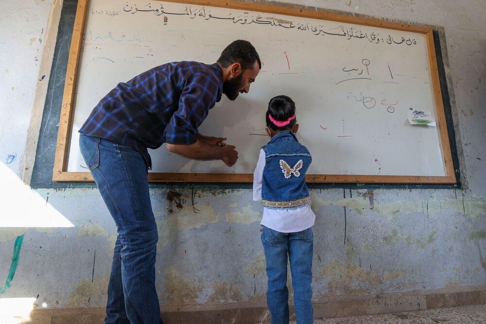 مدرس يساعد تلميذة صغيرة في اليوم الأول من المدرسة في قرية بريف إدلب شمال غرب سوريا، 9 أكتوبر 2021.