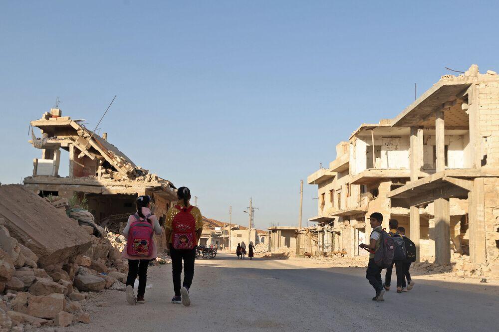 أطفال يمشون بين الأنقاض أثناء حضورهم اليوم الأول من المدرسة في قرية في ريف إدلب شمال غرب سوريا، 9 أكتوبر 2021.