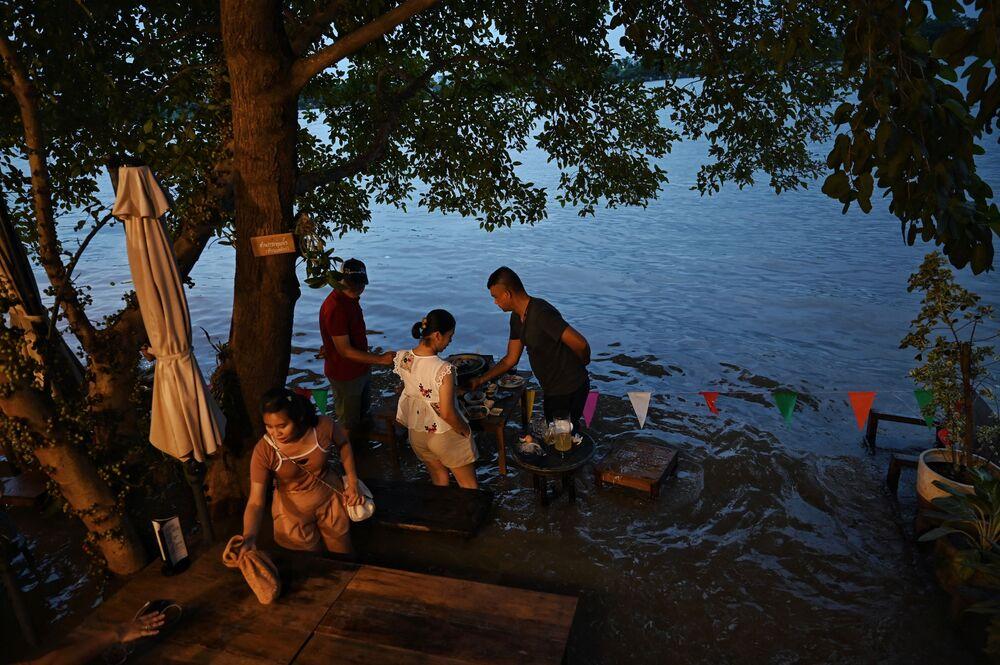 زوار مقهى تشاو فرايا أنتيك (Chaopraya Antique)، حيث تتدفق مياه الفيضانات من نهرتشاوبرايا إلى المطعم في مقاطعة نونثابوري، شمال بانكوك، 7 أكتوبر 2021