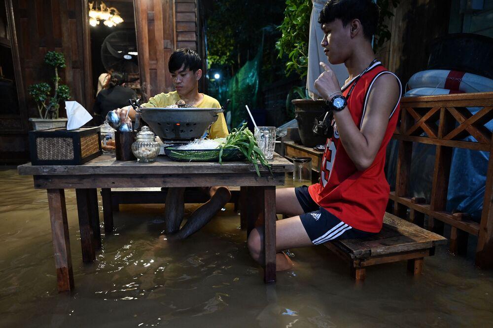 أشخاص يستمتعون بوجبة عشائهم في مقهى تشاو فرايا أنتيك (Chaopraya Antique)، حيث تتدفق مياه الفيضانات من نهر تشاو فرايا إلى المطعم في مقاطعة نونثابوري، شمال بانكوك، 7 أكتوبر 2021