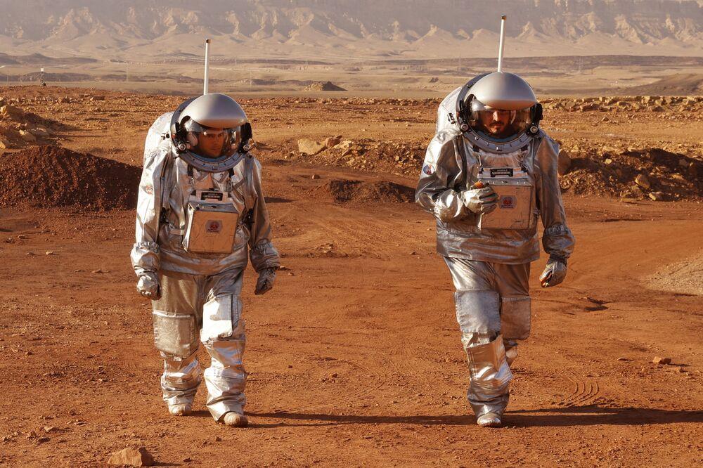 رواد فضاء من فريق من أوروبا وإسرائيل يرتدون بدلات فضائية خلال مهمة تدريبية لكوكب المريخ، في موقع يحاكي محطة خارج الموقع في حفرة رامون في متسبي رمون في صحراء النقب جنوب إسرائيل في 10 أكتوبر 2021.