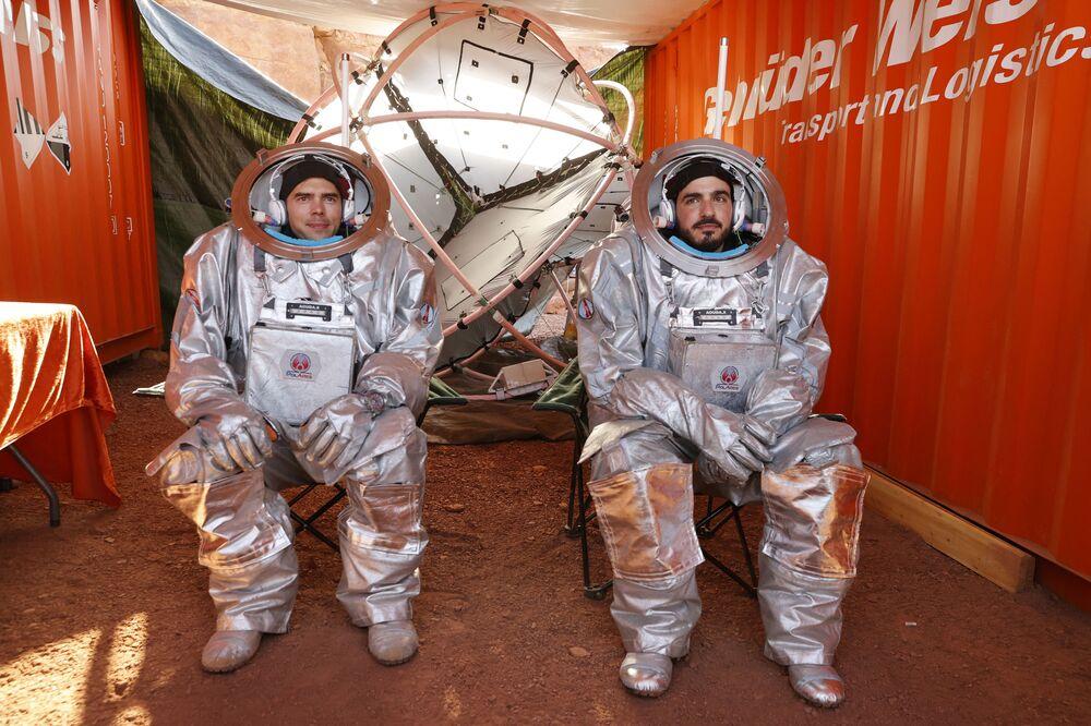 اثنان من رواد الفضاء يجلسان داخل ما يشبه قمرة المركبة الفضائية، أثناء التدريب في موقع يحاكي محطة فضاء في حفرة رمون في متسبي رمون في صحراء النقب جنوب إسرائيل، 10 أكتوبر 2021.