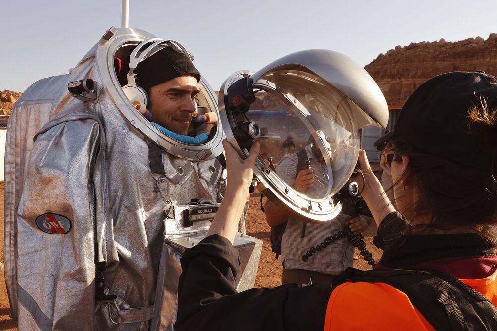 تقنيون يساعدون رواد الفضاءعلى ارتداء زي رائد فضاء، أثناء التدريب في موقع يحاكي محطة فضاء في حفرة رمون في متسبي رمون في صحراء النقب جنوب إسرائيل، 10 أكتوبر 2021.