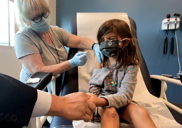 طفلة تتلقى تلقيحا لواحد من جرعتين مخفضتين 10 ميكروغرام من لقاح فايزر-بيونتيك المضاد لفيروس كورونا خلال تجربة في جامعة ديوك في دورهام بولاية نورث كارولينا، الولايات المتحدة، 28 سبتمبر/ أيلول 2021