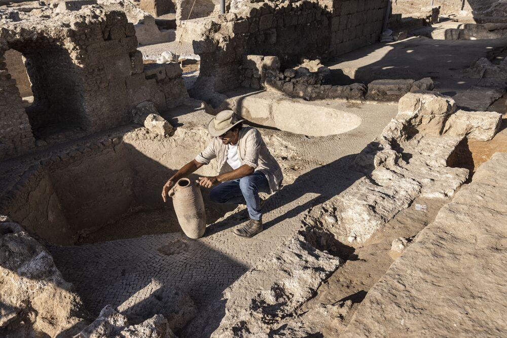 أفشالوم دافيدسكو، من سلطة الآثار الإسرائيلية، يفحص جرة في مجمع صناعة نبيذ قديم ضخم يعود تاريخه إلى حوالي 1500 عام في يفنه، جنوب تل أبيب، إسرائيل، 11 أكتوبر2021.