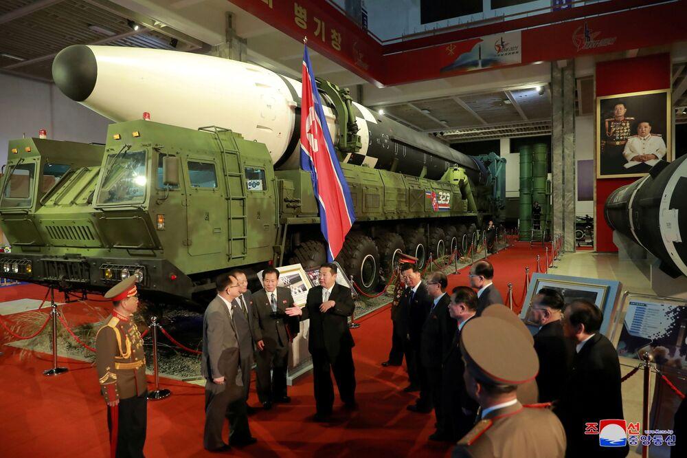 زعيم كوريا الشمالية كيم جونغ أون إلى المسؤولين بجوار الأسلحة والمركبات العسكرية المعروضة، بما في ذلك الصواريخ الباليستية العابرة للقارات (ICBM)، في معرض تطوير الدفاع، في بيونغ يانغ، كوريا الشمالية، 12 أكتوبر 2021 .