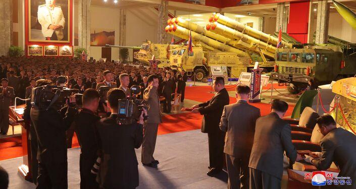 زعيم كوريا الشمالية كيم جونغ أون يتحدث إلى المسؤولين بجوار الأسلحة والمركبات العسكرية المعروضة، بما في ذلك الصواريخ الباليستية العابرة للقارات (ICBM)، في معرض تطوير الدفاع، في بيونغ يانغ، كوريا الشمالية، 12 أكتوبر 2021 .