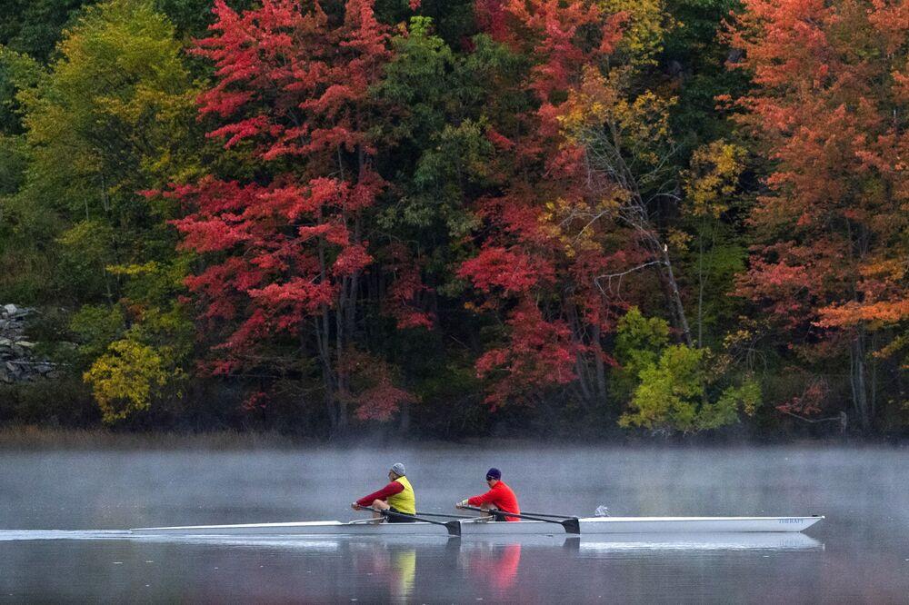 ينزلق زوج من المجدفين على نهر أندروسكوجين في برونزويك بولاية مين، حيث تغيرت أوراق الشجر إلى ألوان الخريف، 10 أكتوبر 2021.
