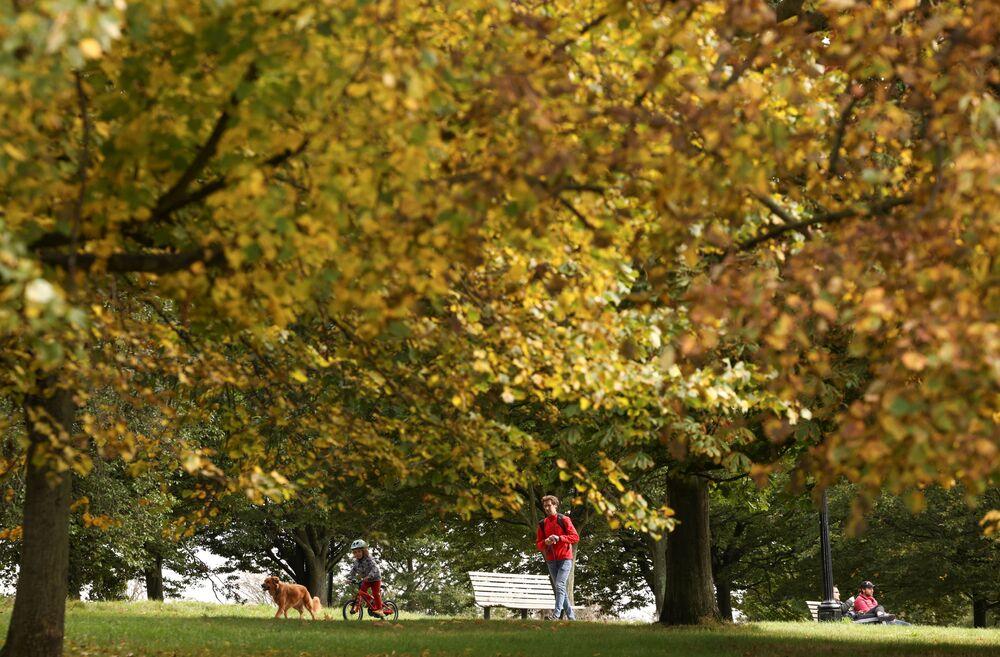 يسير الناس عبر تل تريمورس هيل حيث تبدأ الأشجار في إظهار ألوانها الخريفية في لندن، بريطانيا، 10 أكتوبر 2021.