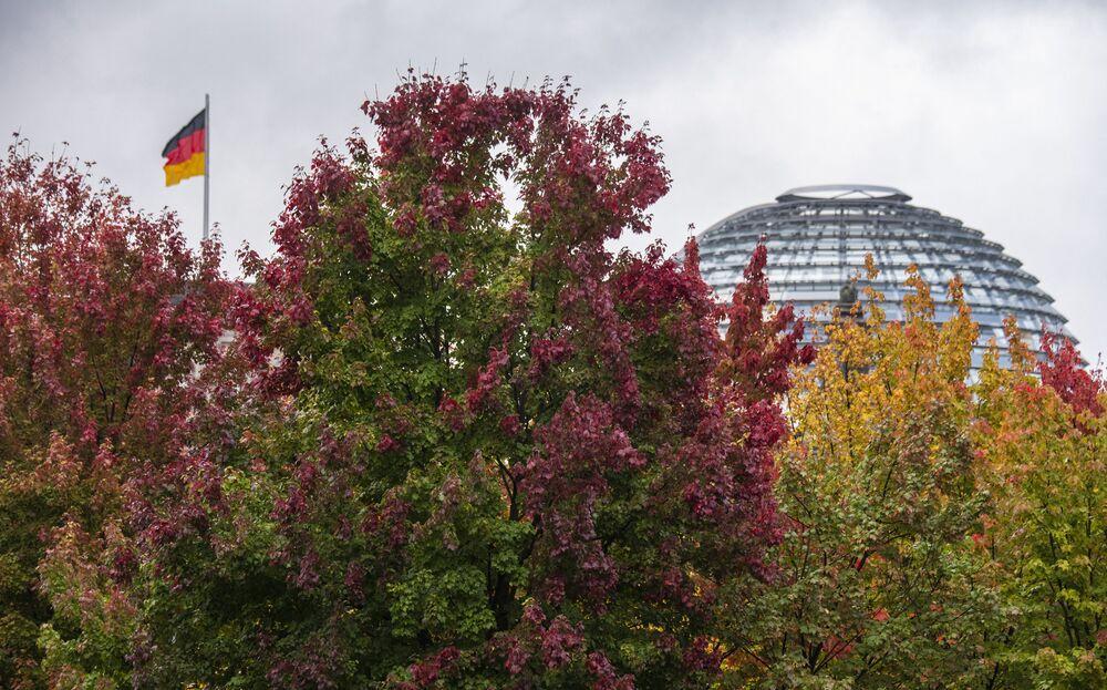 تتزين الأشجار بألوان زاهية أمام مبنى الرايخستاغ حيث يرفرف العلم الألماني، بينما الخريف في برلين، ألمانيا 12 أكتوبر 2021.