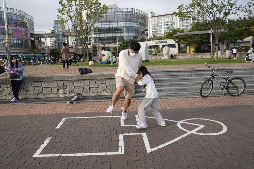 الأب وابنته يلعب لعبة الحبّار، من مسلسل لعبة الحبّار (Squid Game) المعروض على شبكة نتفليكس، في حديقة لعبة الحبّار في مدينة غويانغ، كوريا الجنوبية ، 11 أكتوبر2021.