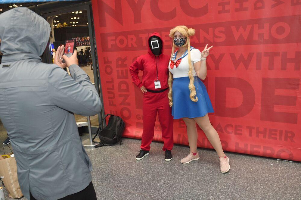 أشخاص يرتدون أزياء شخصيات من مسلسل لعبة الحبّار (Squid Game) المعروض على شبكة نتفليكس ومسلسل الكرتون سايلور مون، خلال مهرجان كوميك كون 2021 في نيويورك، الولايات المتحدة، 9 أكتوبر2021.