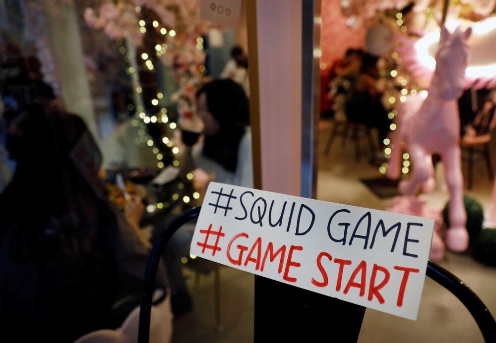 لافتة مكتوب عليها فلتبدأ اللعبة على باب مقهى براون باتر لبيع حلوى البسكويت (Honeycomb) من طفولة الكوريين التي كانت ضمن مسلسل لعبة الحبّار (Squid Game) المعروض على شبكة نتفليكس، في سيؤل، كوريا الجنوبية، 1 أكتوبر 2021.
