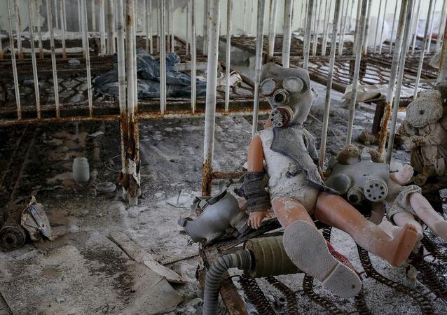 دمية أطفال ترتدي قناع ضد الغاز بين ركام منزل دُمر فيي مدينة بريبيات بالقرب من المحطة النووية تشيرنوبل، أوكرانيت 28 مارس/ آذار 2016.