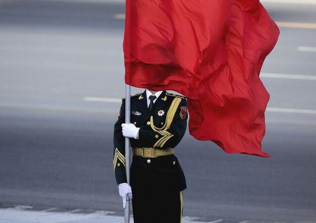 العلم الصيني يلف وجه أحد جندو الحرس الوطني عندما وصل رئيس الوزراء رانيل ويكرميسنغل في بكين، 7 ابريلط/ نيسان 2016.