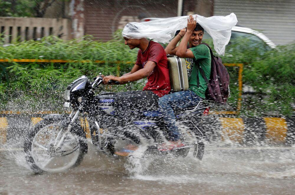 شابان تحت امطار غزيرة في الهند، 27 يوليو/ تموز 2016
