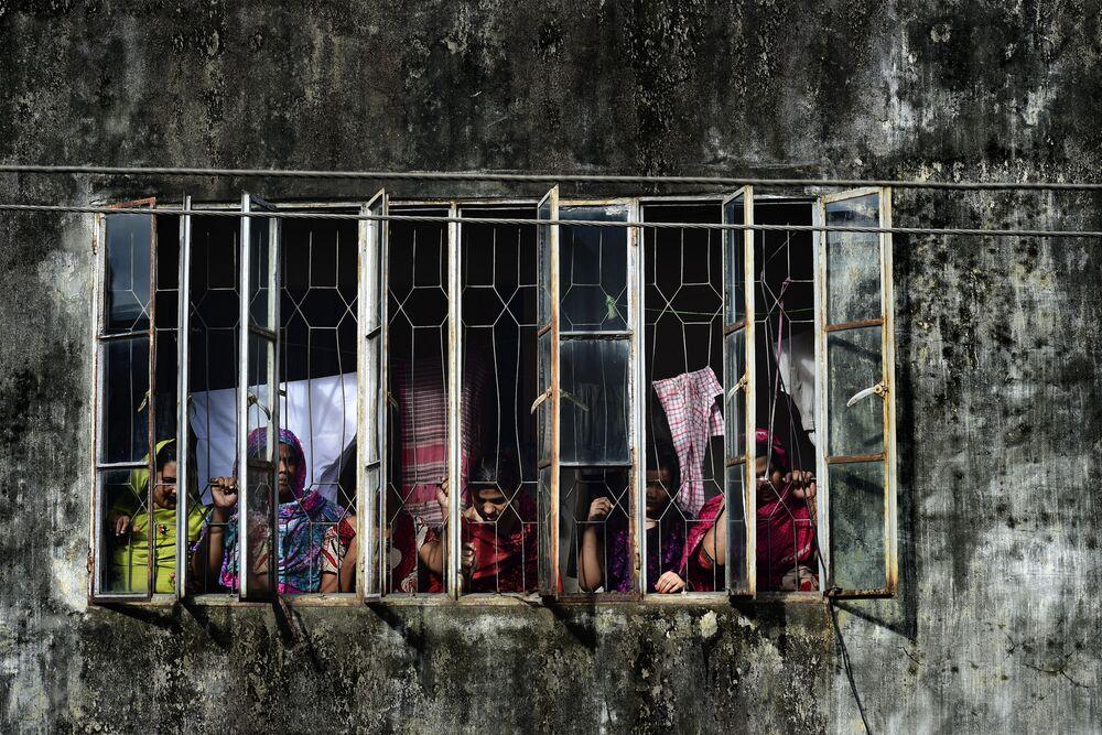 البنغلاديشيون ينظرون إلى المبنى المجاور، حيث قضت الشرطة الهندية على المتطرفين الإسلامين، 26 يوليو/ تموز 2016