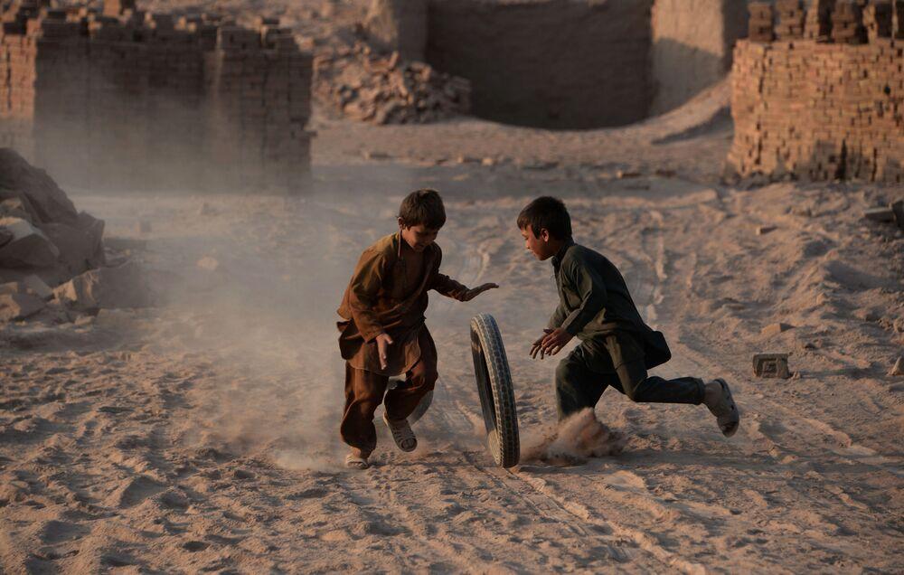 أطفال أفغانستانيون يلعبون بالعجل، 27 يوليو/ تموز 2016
