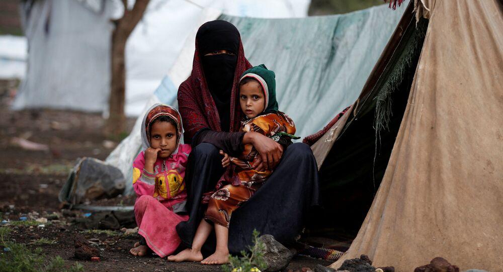 امرأة مع طفلتيها تجلس قبالة خيمتها بمخيم للنازحين في أحد شوارع مدينة صنعاء، اليمن 15 أغسطس/ آب 2016