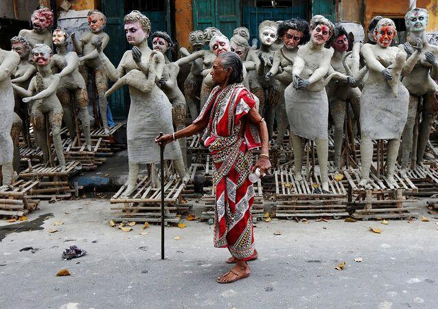 امرأة هندية تقف أمام تمثايل لشخصيات هندية، التي سيتم وضعها حول الإلهة كالي خلال مهرجان كالي-بودجا في كلكتا، الهند 24 أكتوبر/ تشرين الأول 2016