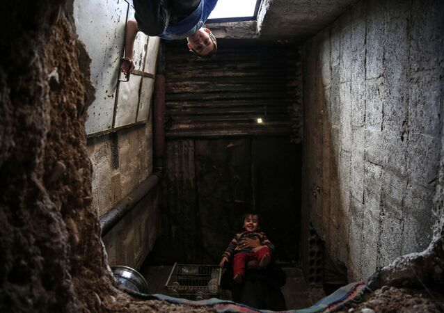 أطفال سوريون يجلسون بمدخل ملجأ أبو عمر في بلدة دوما، في شرق دمشق، 30 أكتوبر/ تشرين الأول 2016