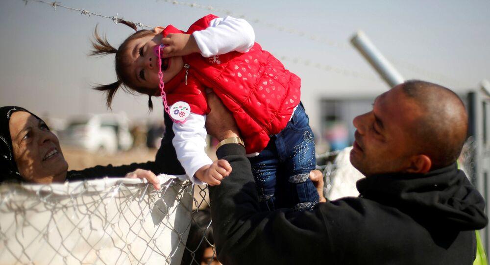 نازح عراقي من الموصل، يمرر ابنته لترى جدتها من خلال عازل بمخيم للنازحين، العراق 28 نوفمبر/ تشرين الثاني 2016