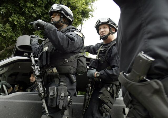 FBI agents in riot gear get information from a Los Angeles Police Department police officer (R) as they head towards the Mexican consulate in Los Angeles
