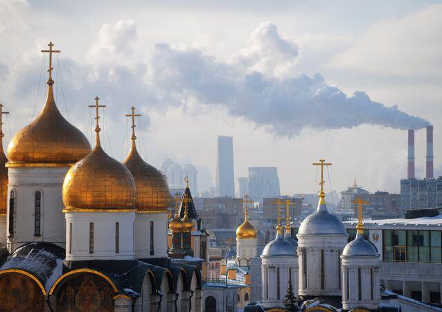 كثدرائية أوسبينسكي (يسار)، وكنيسة الرسل الاثني عشر. في الخلفية: ناطحات السحاب في مدينة موسكو.