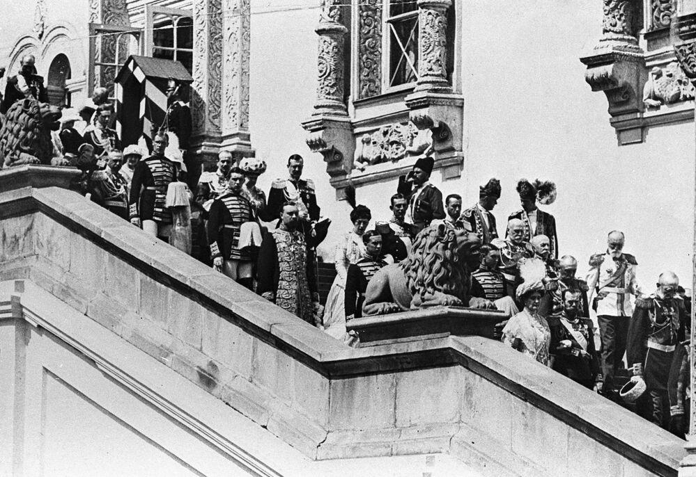 الإمبراطور الروسي نيكولاي الثاني والامبراطورة ألكسندرا فيودوروفنا (أسفل يمين الصورة) يخرجون من غرفة غرانوفيتايا إلى الشرفة الحمراء خلال مراسم الاحتفال بالذكرى الـ 300 منذ تولي سلالة رومانوف الحكم، عام 1913