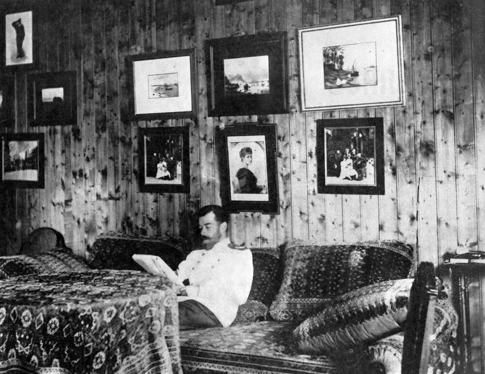 الإمبراطور الروسي نيكولاي الثاني يقرأ كتاباً جالساً على الأريكة في منزله للصيد