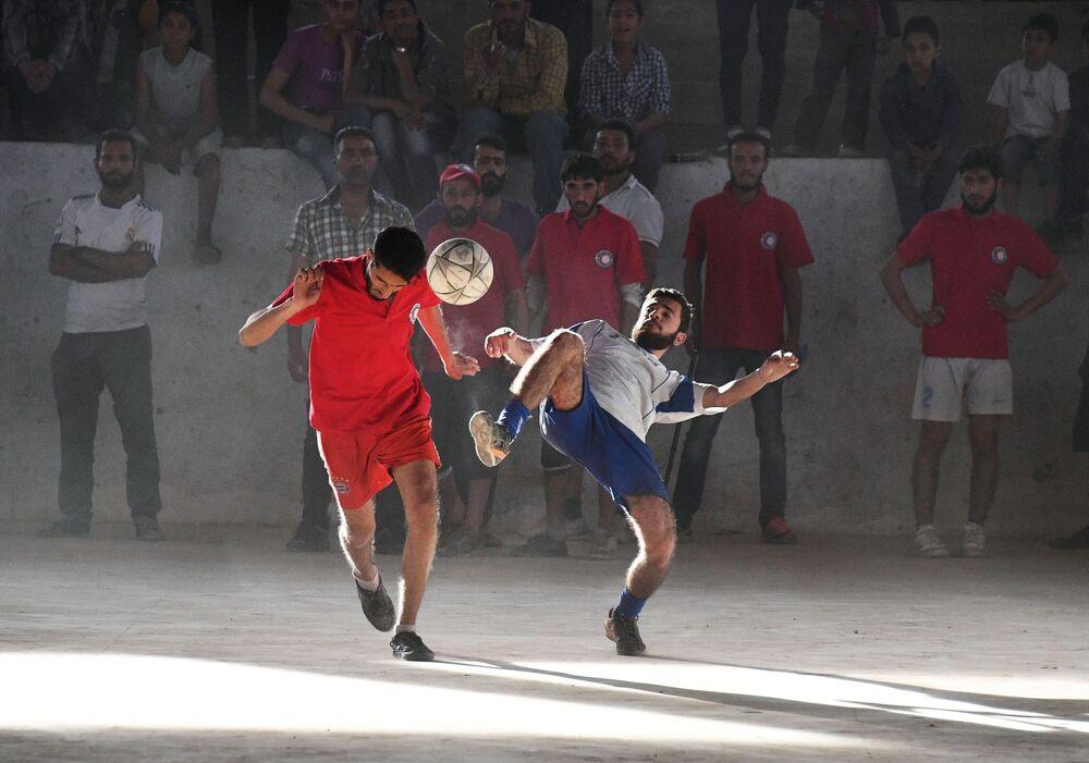 لاعبو كرة القدم خلال مباراة بين فريق جمعية الهلال الاحمر وفريق جمعية الصليب الأحمر في دير الزور، سوريا