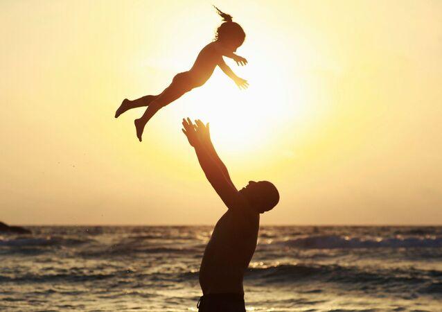 Мужчина играет с дочкой на пляже во время празднования Ураза-байрама в Ашкелоне, Израиль