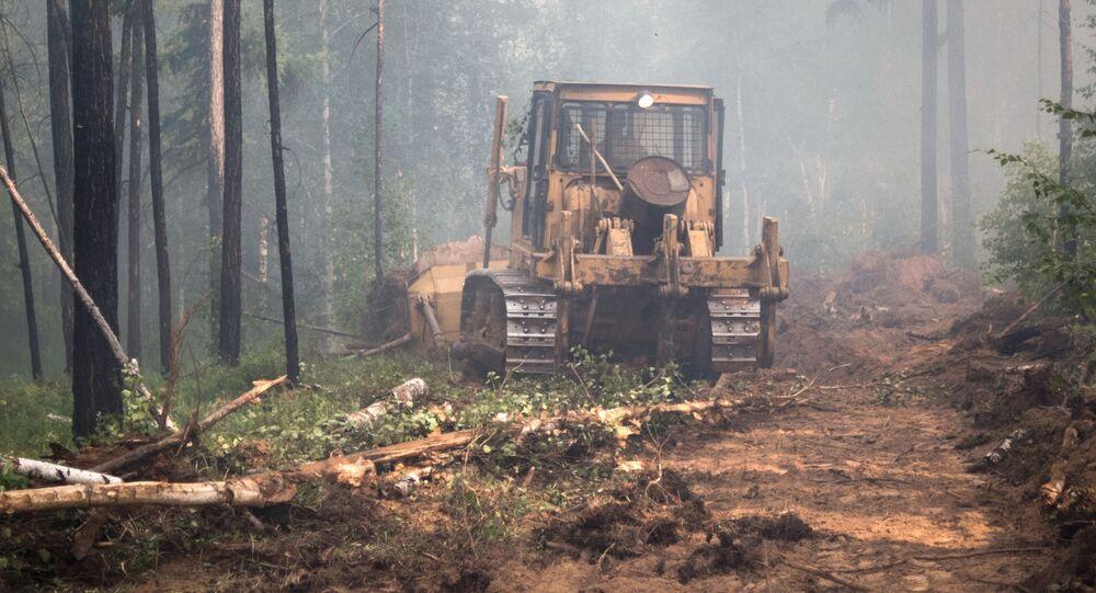 إنشاء عازل ترابي بواسطة جرافة خلال تصفية حرائق الغابات في ضواحي قرية غيتشورا بجمهورية بورياتيا، روسيا الاتحادية