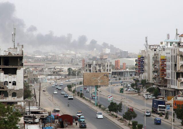الدخان يتصاعد من مخزن قطع غيار السيارات أصيب بقذائف خلال الصراع في مدينة عدن الساحلية