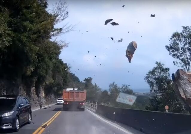 سقوط صخرة ضخمة وسط طريق ممتلئ بالسيارات