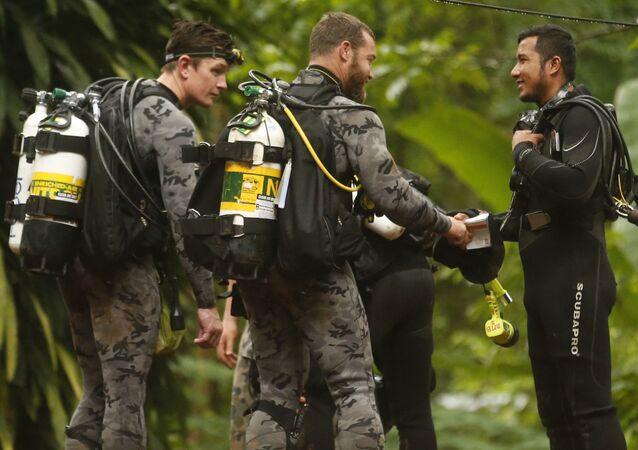 موظفو الشرطة الفيدرالية الأسترالية يتحدثون مع أحد عمال الإنقاذ التايلنديين قبل بدء عملية الإنقاذ