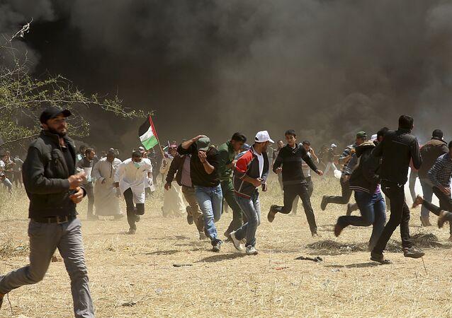 متظاهرون فلسطينيون يهربون من الغاز المسيل للدموع الذي أطلقه الجنود الإسرائيليون خلال اشتباكات مع القوات الإسرائيلية على طول حدود غزة مع إسرائيل ، شرق خان يونس ، قطاع غزة ، الجمعة 6 أبريل 2018