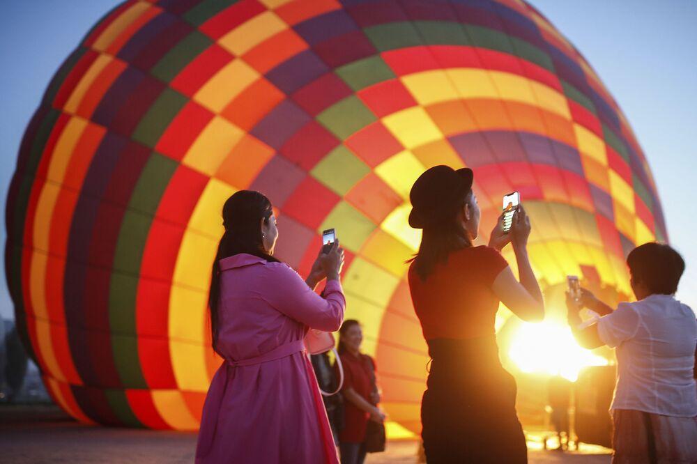 رسياح يلتقطون صورا للمنطاد قبل انطلاقه  في رحلة في كابادوكيا، تركيا